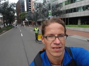 im vordergrund: ciclovía-teilnehmer mit migrationshintergrund - im hintergrund: ordnungskraft