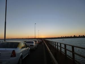 """""""Grenzstau auf der Brücke über den Rio Paraná im Abendrot; in Öl"""" schöner Gemäldetitel"""