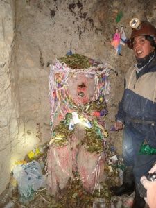"""der """"Tío""""/Teufel. Hier werden Kokabläter, Zigaretten u Alkohol geopfert. An der Wand ist Lamablut (die dunklen Spritzer) zu erkennen."""
